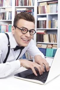 Computer nerd. Side view of excited young man in shirt and bow tie typing something on computer and looking at camera with smile